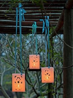 Luminárias de parafina com minivelas foram presas em uma treliça. Boa dica para uma festa no jardim