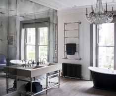 Yes; yes, you should. Your existent vanity mirrors can easily be 'antiqued' using muriatic acid and/or an aerosol paint stripper. A decorative smaller mirror can then be hung atop the surface over the sinks. Don't get rid of all the natural light in that small space!