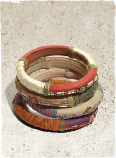 Artisan-made, brightly beaded bangles are wrapped in silk and suede, then ornamented with delicate beadwork. They look lovely when stacked together.