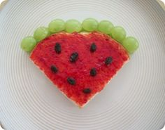 """Watermelon"" sandwich - peanut butter on the inside and strawberry jelly on the outside, with raisins on the top and green grapes (cut in half) to make the rind. : )"