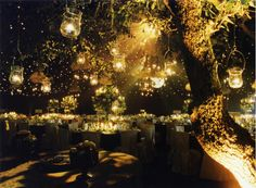 Jars from trees with long lasting tea lights mixed with lights on tables
