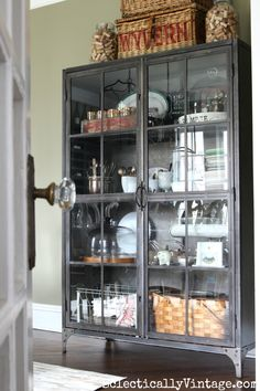 Love this metal glass front industrial cabinet from World Market - perfect for storage and display in the dining room eclecticallyvintage.com