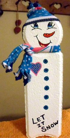 Snowman made by painting a paver brick and adding a few accessories