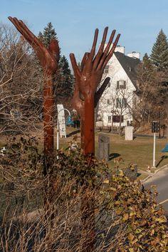 Sculptures dans le Parc portuaire de Trois-Rivières (Québec) avec une vue rapprochée d'une sculpture avec des mains tendues vers le ciel « À la lueur de la ville » de Marie-Josée Roy, 2009