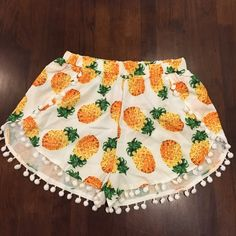 """Pineapple shorts Brand new in packaging. Retail. Super cute and trendy for summer with the pineapples and pom-pom detailing. The shorts themselves do not have sizing in them but the packaging does. I'm typically a medium in most bottoms and the mediums fit me perfectly. The band is very stretchy, allowing lots of room. Since these are white & a little sheer, nude or white underwear would be needed to wear these. Medium bottoms unstretched are about 13"""".  Would be perfect with a navy top and…"""