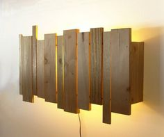 You have to place wooden pieces in vertical form and behind them, put a lamp to complete this project.