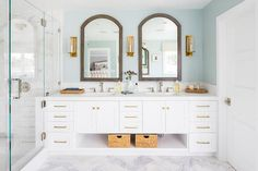 Arch wood mirrors separated by a set of three gold sconces over a white dual washstand accented with brass pulls and vintage hook and spout faucets topped with white marble countertops. Bathroom Interior, Best Bathroom Vanities, Amazing Bathrooms, Bathroom Renovations, White Vanity Mirror, Wood Mirror Bathroom, Small Bathroom Remodel, White Vanity Bathroom, Bathroom Mirror Design