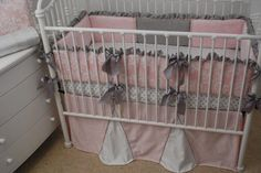 Grey ruffles and ties on the pink crib bumper