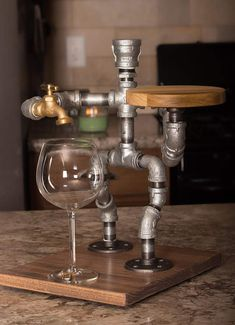 I would make the wood bigger, drill two holes and carve out a slot for two wine glasses Whiskey Dispenser, Alcohol Dispenser, Beverage Dispenser, Steampunk Lamp, Iron Pipe, Pipe Lamp, Pipe Furniture, Metal Art, Home Projects