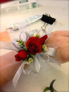 Red Rose Corsage with Silver Ribbon and White Wax Flower Accent on a Pearl Bracelet.  Englewoodflorist.net