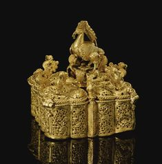A FINE GOLD OPENWORK SPICE BOX, INDIA, 17TH CENTURY  Estimate: 25,000 - 35,000 GBP   of square form, comprising four tri-lobed compartments, each surmountedby asmall bird, a centralised locking finial in the shape of a large peacock, the openwork decoration of stylised birds within naturalistic flower scrolls, the underside decorated with rigorous interlacing foliate scrolls comprising of palmettes and split palmettes  7cm. width  8cm. height