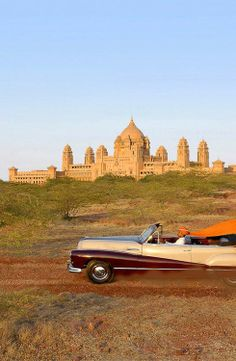 The Umaid Bhavan Palace and hotel in the background. One of the royal automobiles in the foreground. The erstwhile maharaja and his family still reside here. Jodhpur, Rajasthan.