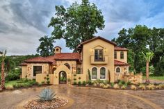 This isnt a bad spanish style home. I would include more trees in the front though and do lighter stucco.
