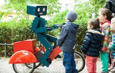 Roboter Walking Act Hugo ist fertiggestellt Pfiu! Es ist geschafft. Endlich ist es soweit. Hugo der Roboter hat ein Fahrrad bekommen. Genauer gesagt ein Dreirad. Und damit ist das kleine Kerlchen mobil. Aber schaut selbst: