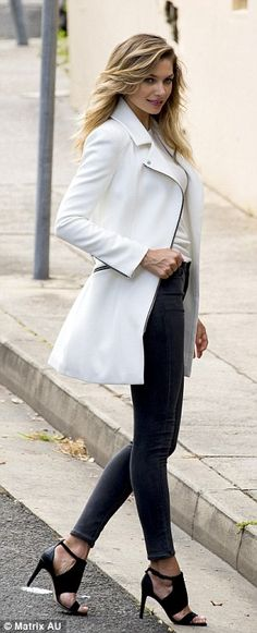 White hot:A chic white trench coat was added on to a previous look, and the blonde bombshell didn't let the warm weather effect her poses