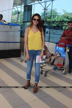 Also spotted at the airport was Bollywood actress Esha Gupta, bright as sunshine in a sleeveless yellow top worn with blue jeans, denims and boots.