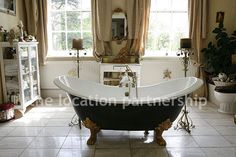 Spacious and light bathroom with large Georgian windows and a freestanding bath in a French boudoir feeling atmosphere