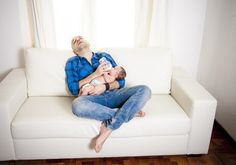 new father exahusted alseep while feeding his newborn baby