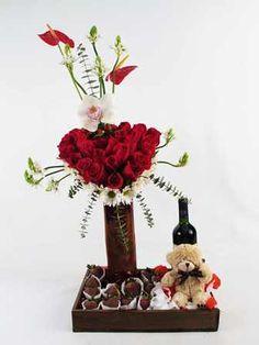 Original arreglo floral con rosas que forman un corazón, orquidea y anturios, acompañado de deliciosas fresas bañadas con chocolate, peluche y vino.