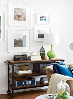 Vintage underwood typewriter, old suitcases, beverages crate, and a pop of color from the table lamp makes for a nice grouping for this console table. (styleathome.com)