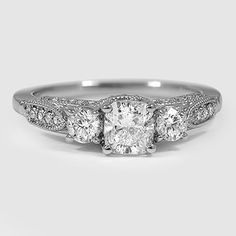 Delicate vintage-inspired details on a timeless three stone engagement ring.