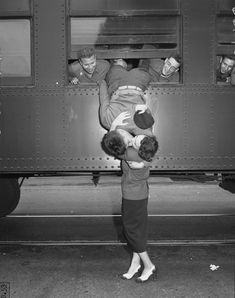 California National Guardsman hanging out window of train, kissing his wife good-bye, 1950