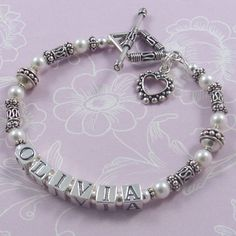 Mother's Name Bracelet - M03  White Swarovski pearls and beautiful Bali sterling silver beads are combined to create this classic bracelet. Custom made with your children's names, your choice of clasp, charms and number of strands, sized to fit.  Main picture shows the M03 design with a Bali diamond toggle clasp and dotted heart outline charm. Large letter blocks. Pearl colour – white.