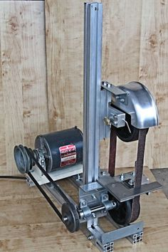 Belt Grinder by prmindartmouth -- Homemade belt grinder constructed from aluminum extrusions, steel plate, pulleys, caster wheels, bearings, and a spark guard adapted from an aluminum pot. Powered by a 1/3hp motor. http://www.homemadetools.net/homemade-belt-grinder-28