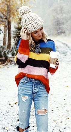 #fall #outfits women's black, blue, yellow, pink, and red striped sweater, distressed blue stone-washed denim skinny jeans, and beige knit cap