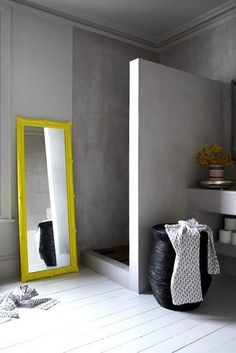 Concrete bathroom with yellow mirror via The Minimalist