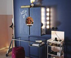 Bild einer Schminkstation bestehend u. a. aus einem Schrank, einem VITTSJÖ Laptop-Tisch in Schwarzbraun/Glas und einem Platz für den Rollwagen aus dem Badezimmer. Wände und Schrank sind blau gestrichen.