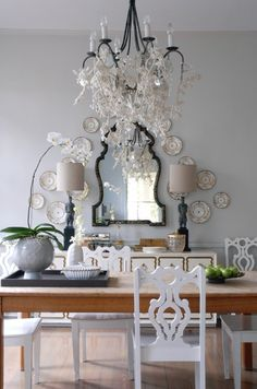 Glamorous White Dining Room    Let antiques shine in a neutral room.      A simple farm table, heirloom china arranged around a chinoiserie mirror, and a whimsical felt garland strewn through a chandelier create an inviting space for entertaining.    Photographer:  Kerri McCaffety    Source: Big, Easy Style (2011 Clarkson Potter) by Bryan Batt, available through Amazon.ca.  Designer: Bryan Batt