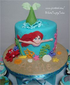 The Little Mermaid Cake and Cupcake Tower - Ariel, The Little Mermaid, cake and cupcake tower made for a sweet little girl's 5th birthday. I was inspired by the lovely cake made by Angela (Angel Food 4 here on CC), and she was gracious enough to allow me to use her design. I also made 40 fondant sea life cupcake toppers. I love my cupcake stand, and cover it with matching scrapbook paper to match the theme of the party. Thank you so much for looking!