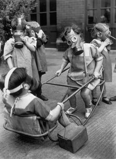 Small children in a playground wearing their gas masks around 1940.     (those little shoes... the size of their hands... contrasted with the immensity, literal & figurative, of the gas masks... So sad)