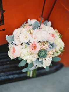 Roses, succulents, dusty miller and more! Love this bridal bouquet on our vintage truck! Photo By - Britta Marie Photography