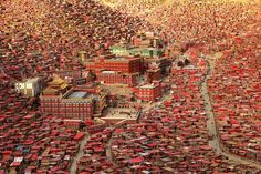 Picture of a sprawling complex of small, red dormitories surrounding a monastery, Tibet, China