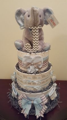 Blue and grey elephant diaper cake. It's a BOY! Baby shower gift/baby shower centerpiece.  Includes 65 diapers,  3 receiving blankets,  1 pair of scratch mits,  2 MAM pacifiers,  4 pair of socks, initial letter,  plush elephant.  Visit my Facebook page Simply Showers for more pics and orders. Thanks Kim