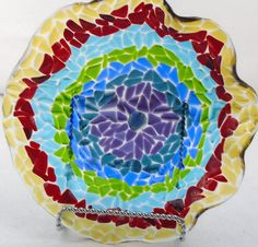 """Multi-Colored Mosaic Decorative Ruffled Bowl Handcrafted Fused Glass. This decorative bowl of transparent pieces of purple, blue, green, aqua, red, and amber is a mosaic design with very slight texture. It is a beautiful bowl that can be used as a center piece, fruit bowl, or as a serving piece. It is 10.25"""" in diameter and 3"""" high. Hand washing is recommended.. Includes artist's mark on the bottom of the glass."""
