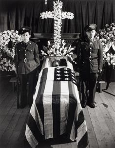 Two Japanese American soldiers visiting their families at Heart Mountain internment camp ironically stand honor guard beside the casket of a WWI vet who died in the Wyoming camp. While 120,000 Japanese-Americans were interned for up to 3 years, 33,000 others served in the U.S. armed forces, including the much decorated 100th Battalion Combat Team, which fought in Europe.