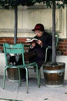 An elderly woman reading outdoors, tucked between two potted trees. People Reading, Woman Reading, I Love Reading, I Love Books, Books To Read, My Books, Foto Poster, World Of Books, Lectures