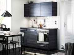 Moderne, mørkebrunt køkken med TINGSRYD fronter og en mørk bordplade