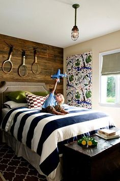 I really dig the contrast of the rustic wood planked wall against the bold, striped bedding and panel of fabric hanging on the wall