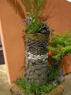 Philadelphia Flower Show 2012 - cool way to elevate a pot - use strong wire mesh formed as a tube, fill with nature and a hidden pot with plants