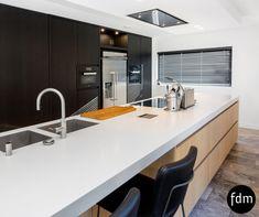 Deze greeploze moderne eiken zwart beits hoge kastenwand is gecombineerd met een greeploze eiken white wash kookeiland. Het Corian aanrechtblad de Bora inductiekookplaat en de RVS koelkast maken het geheel helemaal af.