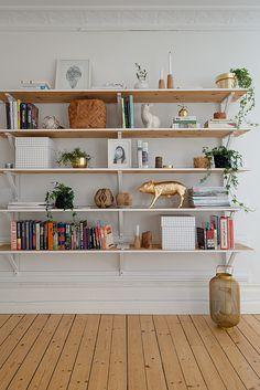 Väggfast bokhylla på diskreta konsoler. Trärena hyllplan med vitmålade fronter.