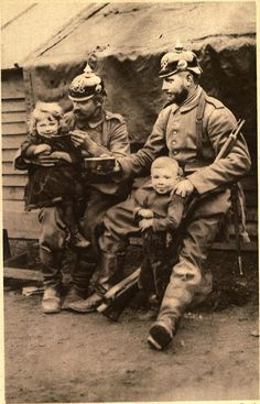 German soldiers on outpost duty near Antwerp, sharing their food with Belgian orphans, published in 1915.
