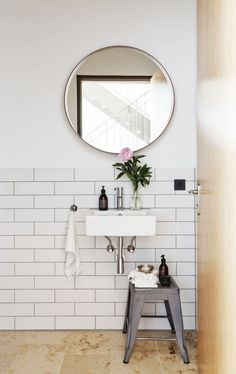 love this bathroom with the simple white subway tiles and round mirror