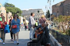 A street guitarist tunes his #guitar before performing near the #Colosseum