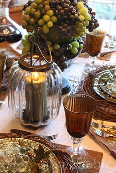 Vineyard tablescape. Love the crystal grapes, grapevine wreath chargers, and the candle hurricanes!
