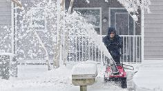 Deanna Ruffin of Grady Management uses a snow blower to clear sidewalks at an apartment complex on Pilot House Drive as snow continues to fall on Thursday morning in Newport News. (Photo by Kaitlin McKeown / Daily Press)